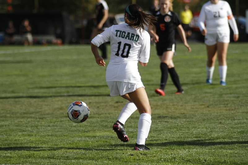 PMG PHOTO: WADE EVANSON - Tigard's Kimberley Meza gathers the ball during the Tigers' nonleague game at Scappoose Tuesday, Sept. 14, at Chinook Park in Scappoose.