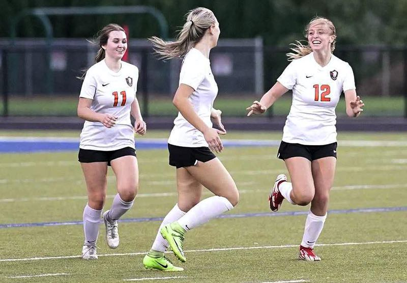 COURTESY PHOTO: JON OLSON - Gladstone's Rhyli Grim (right) is all smiles as she is greeted by Sam Jedrykowski (left) and Alyx DeVeny after scoring one of her three goals in the Gladiators' 3-0 win at Valley Catholic on Tuesday, Sept. 14.