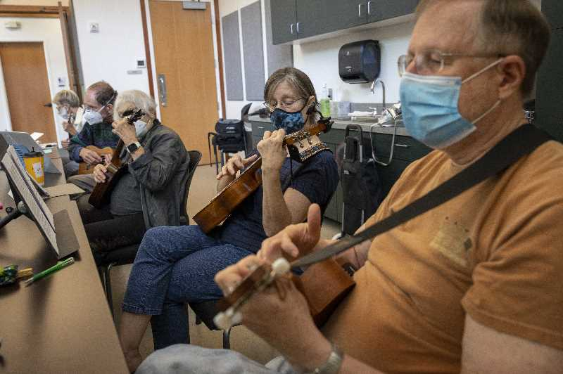 PMG PHOTO: JAIME VALDEZ - Reni and Greg Erk of Aurora play their ukuleles with the rest of the members of the Ukulele Jam at Wilsonville Parks and Recreation Department building.