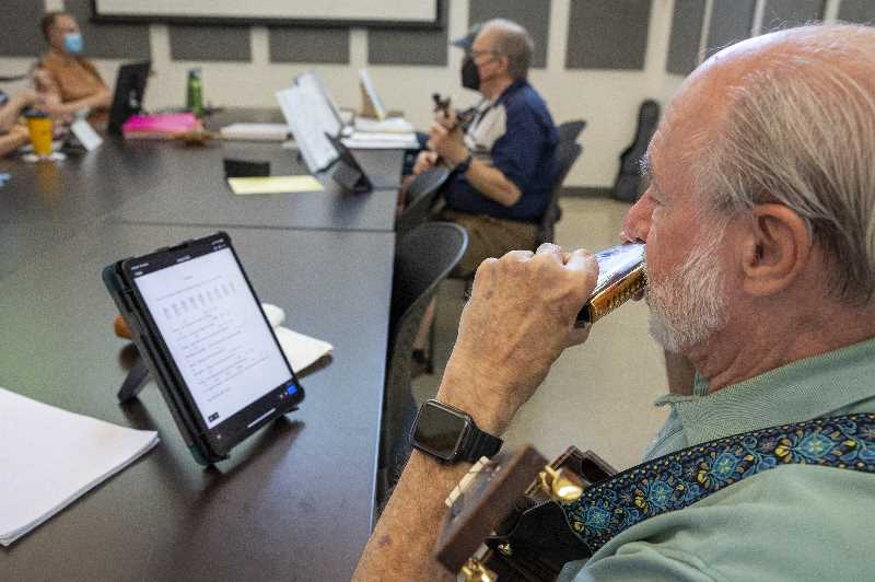 PMG PHOTO: JAIME VALDEZ - Ron McCallister of Charbonneau plays the harmonica while the rest of the members of the Ukulele Jam play songs on their ukuleles.