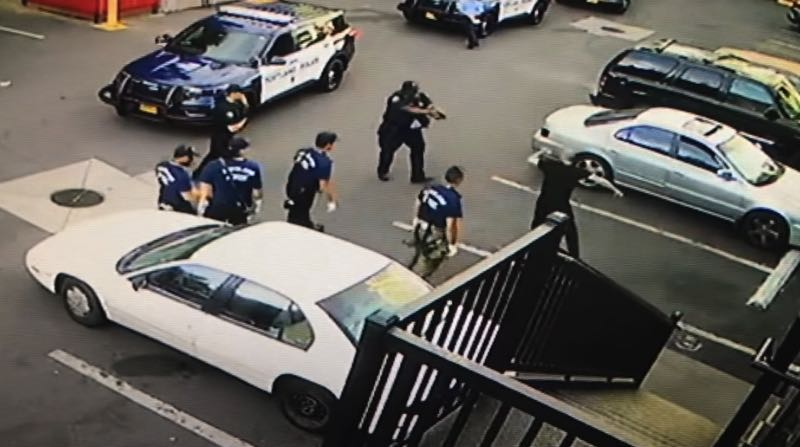 PHOTO COURTESY: PPB - Officer Curtis Brown prepares to open fire on Michael Townsend in the parking lot of a Portland Motel 6 in June.