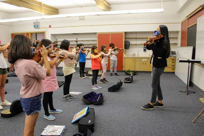 PMG PHOTO: MIA RYDER-MARKS - Instructor Eri Nogueira teaches her class introductory strings on their violins and violas.