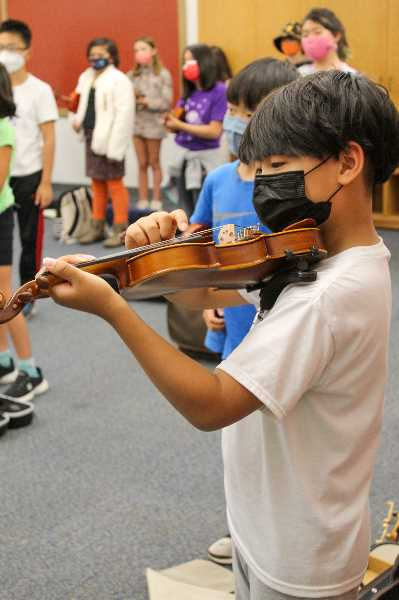 PMG PHOTO: MIA RYDER-MARKS - A student plucks his A string.