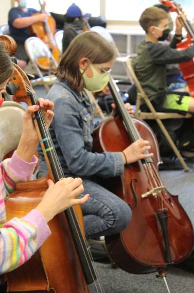PMG PHOTO: MIA RYDER-MARKS - Two students learn their first song on the cello. In two months, they will play their first concert.