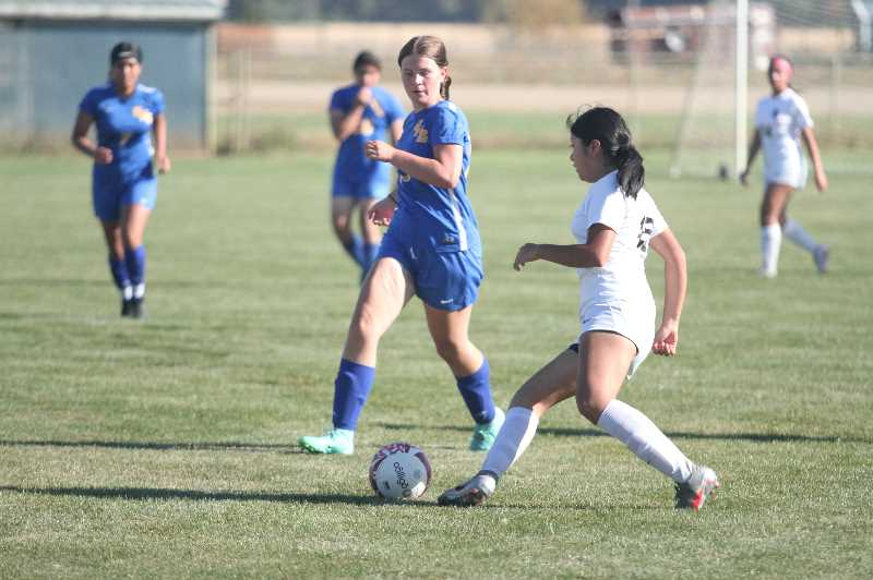 PMG PHOTO: TANNER RUSS - Gervais player Jasmine Rogers challenges a Dayton midfielder for the ball.