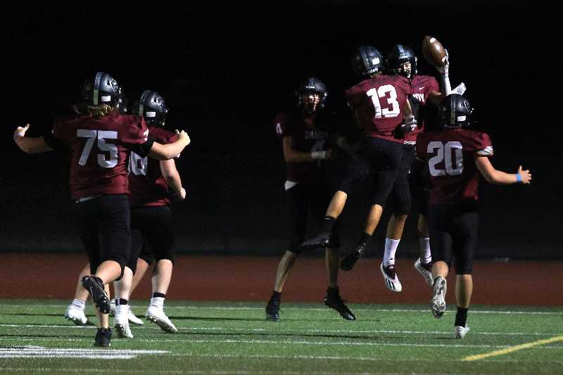 PMG PHOTO: JONATHAN HOUSE  - Sandy High School football players celebrate a touchdown against Barlow on Sept. 1, at Sandy. For the first time in 21 years, Sandy took down its 'big brother' in Barlow with a 14-7 victory.
