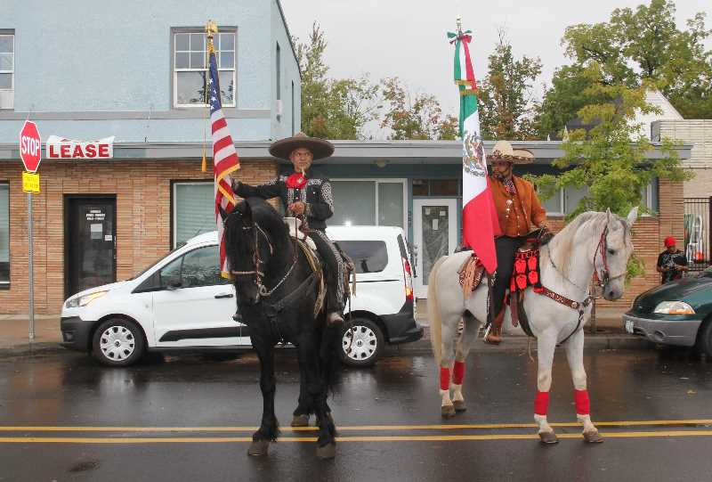 PMG PHOTO: JUSTIN MUCH - The U.S. and Mexican flags are trotted down 1st Street for Woodburn's Hispanic Heritage celebration Saturday, Sept. 18