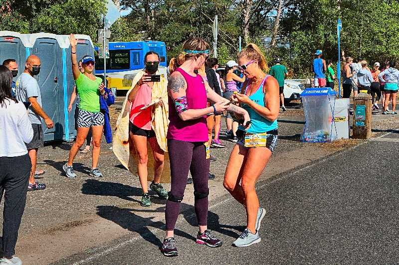 DAVID F. ASHTON - Barbie Haven, of The De-Feeters team, hands off to the next runner, Kelly Miller.