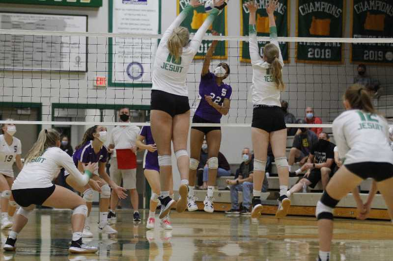 PMG PHOTO: WADE EVANSON - Jesuit's Tess Masingale (16) and Ceanna O'Loughlin (11) block Sunset sophomore outside hitter Thanvi Chilukuri (22) during the two teams' match Thursday, Sept. 16, at Jesuit High School.