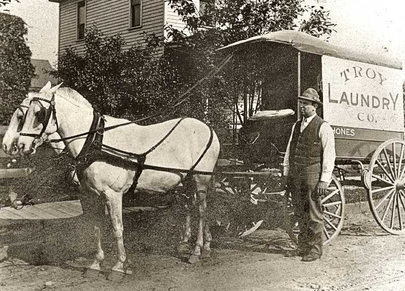 COURTESY OF SMILE HISTORY COMMITTEE - In the early 1900s, women didnt have to rely on a?wash tub and washboard to clean the familys clothes - because laundry companies like this one would pick up a load of wash, clean it, and drop it off the next day.?Now this service, once offered by horse and wagon, is past.?Sellwood resident Charles B. Lance was the driver for the Troy Laundry Company shown here.