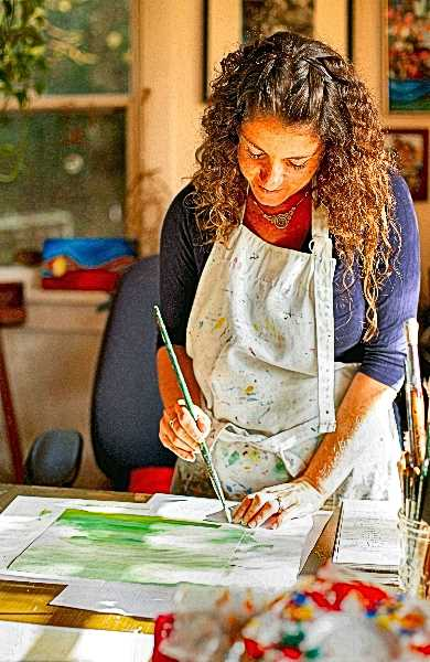 COURTESY OF LUCY FORSTEN - A photo of Lisa Kagan at work in her Woodstock home studio, creating art for her heirloom books and for her books of art and poetry