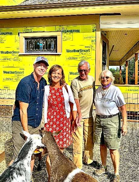 WILSON HACK - From left, here are John Thornton, Dana Hepper, Rick Hepper, and Pam Hepper. The goats - too busy to look at the camera - were enjoying leftover produce donated by New Seasons Market in Sellwood.