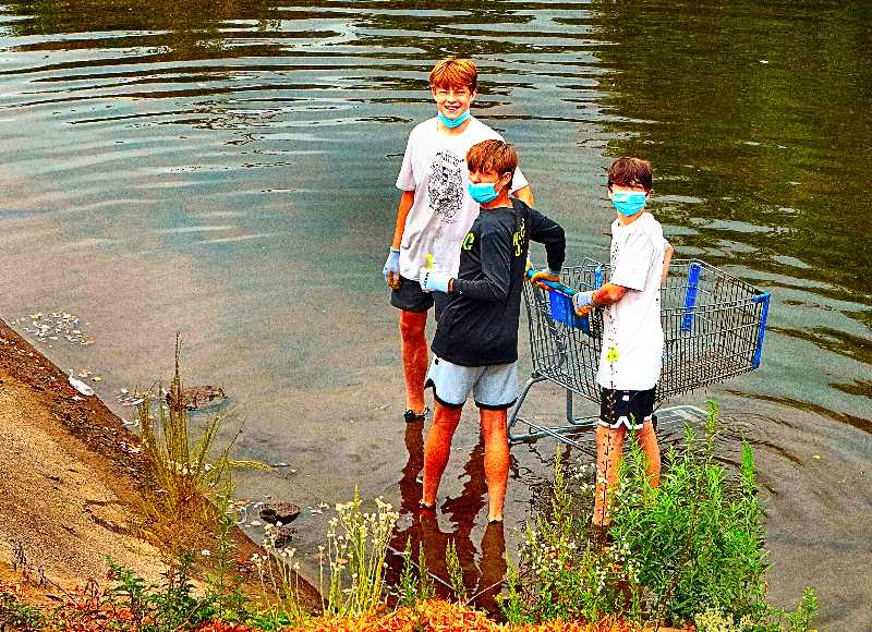 DAVID F. ASHTON - These Johnson Creek Watershed Council volunteers in the 2021 Johnson Creek Clean-up - here pulling a shopping cart out of the stream - were members of the Cleveland High School Soccer Team.