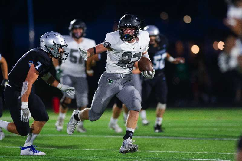 JOHN LARIVIERE - Tigard's Konner Grant (22) of runs for a first down early in the second quarter of their game versus Mountainside Friday night, Sept. 17, at Mountainside High School.