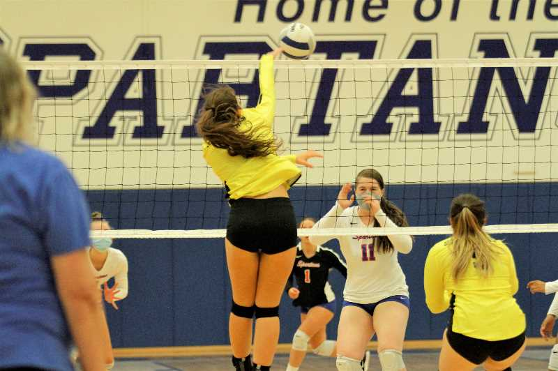 PMG PHOTO: WADE EVANSON - St. Helens senior outside hitter Karlee Webster attacks the net during the Lions' match with Hillsboro Tuesday night, Sept. 21, at Hillsboro High School.