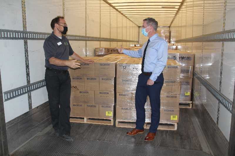 PMG PHOTO: JUSTIN MUCH - Keizer stake of the Church of Jesus Christ of Latter-day Saints President Langdon Smith, right, and Rick Gaupo, chief operating officer of the Marion Polk Food Share, discuss the shipment of food the LDS stake shipped into Salem from Salt Lake City Wednesday, Sept. 22, for distribution to Woodburns AWARE Food Bank.
