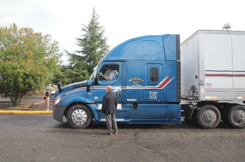 PMG PHOTO: JUSTIN MUCH - Arrival: Dan Kohler of Keizer greets the truck driver delivering food shipped into Salem from Salt Lake City to Marion Polk Food Share Wednesday, Sept. 22. Kohler is a member of the Keizer stake of the Church of Jesus Christ of Latter Day Saints, which arranged the shipment for distribution to Woodburns AWARE Food Bank.