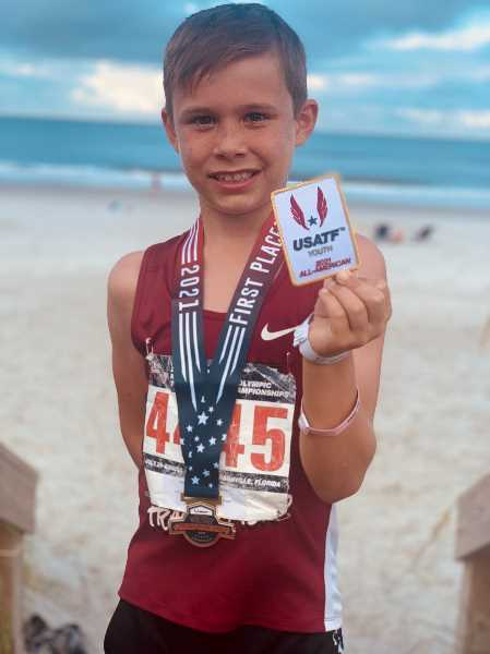 COURTESY PHOTO: ELLINGSON FAMILY - Beckett Ellingson, wearing his championship medal, displays the patch he received at the USATF National Junior Olympic Track & Field Championships in Jacksonville, Florida, in July.