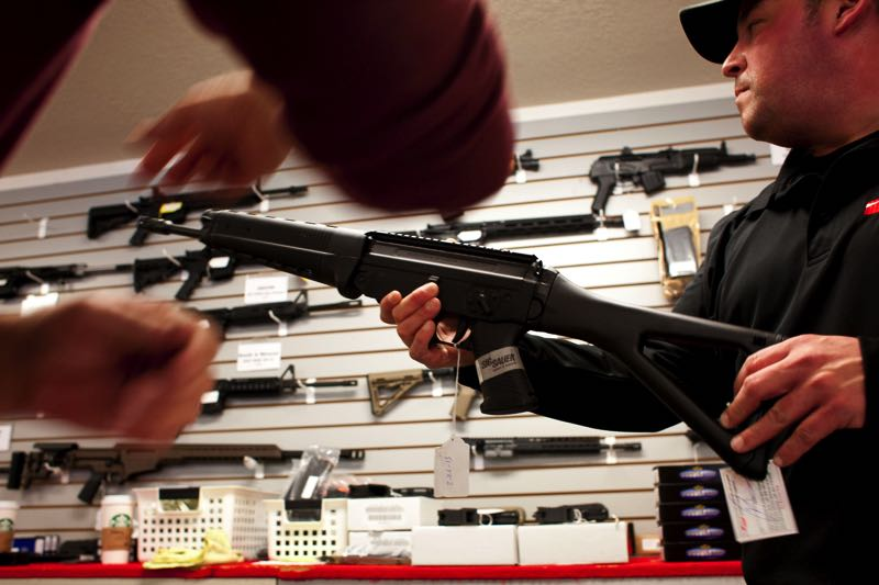 FILE - Don Evans shows a customer a rifle at the Northwest Armory gun shop in Southeast Portland in 2013.