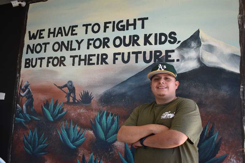 PMG PHOTO: ANGEL ROSAS  - Loeza stands in front of a mural in his coffee shop that reminds him of the sacrifices his family has made to get him to where he is today.