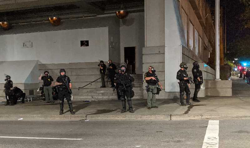 PMG PHOTO: COURTNEY VAUGHN - Police stand guard outside the Multnomah County Justice Center during a Black Lives Matter protest on July 17, 2020.
