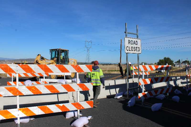 PMG PHOTO: PAT KRUIS - Thursday morning, Sept. 23, ODOT crews put up concrete barriers and construction barricades to close Southwest Eureka Lane and the west stem of Southwest Bear Drive where the roads intersect with Highway 97.