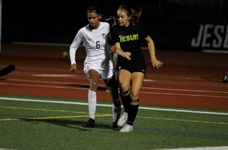PMG PHOTO: WADE EVANSON - Tualatin co-captain Maya Loudd battles a Jesuit attacker during Timberwolves' game against Jesuit Thursday, Sept. 23, at Jesuit High School. Loudd scored the first goal against the Crusaders in 26 games.