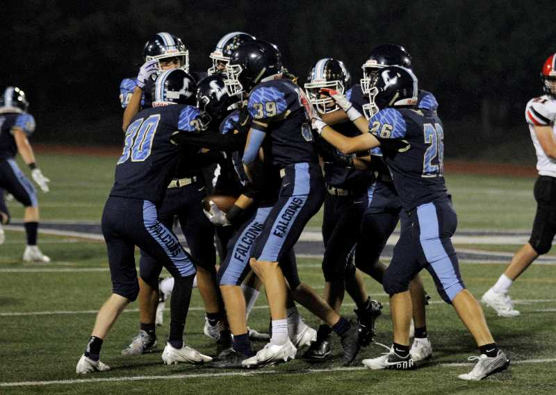 PMG PHOTO: WADE EVANSON - Liberty players celebrate with Tanner Steinbach after the sophomore recovered an onside kick late in the Falcons' game against North Medford Friday, Sept. 24, at Liberty High School.
