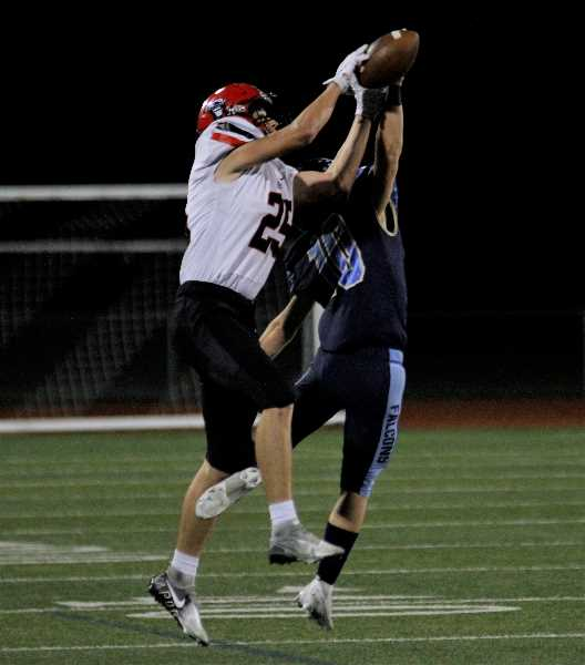 PMG PHOTO: WADE EVANSON - Liberty defensive back Zain Kiser battles North Medford's Bryce Dyer for a pass attempt during the Falcons' game against North Medford Friday, Sept. 24, at Liberty High School.