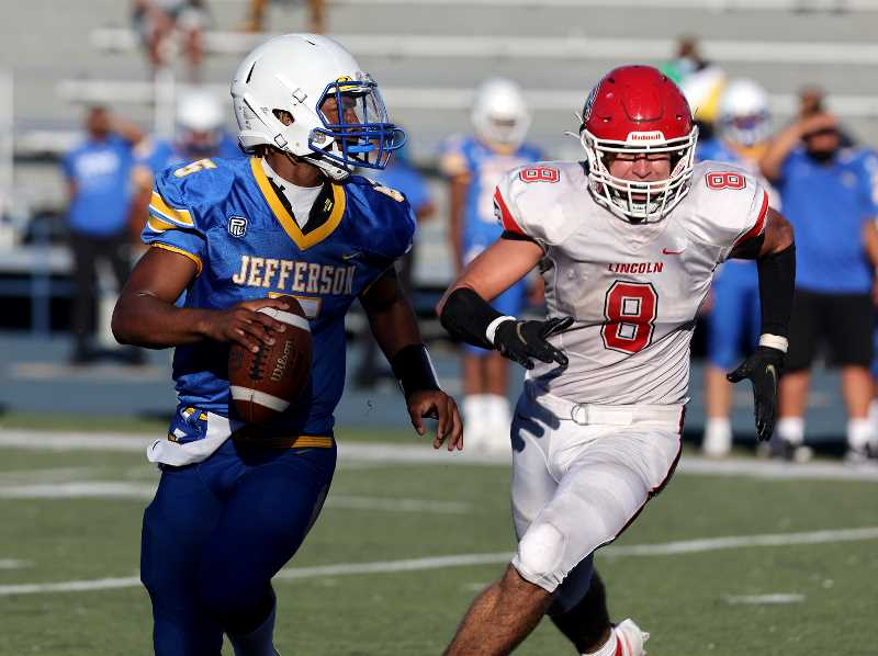 PMG PHOTO: JONATHAN HOUSE - Jefferson quarterback Dondrae Fair, left, looks to pass downfield with Brady Kopetz of Lincoln in pursuit Friday, Sept. 24, at Jefferson High School.