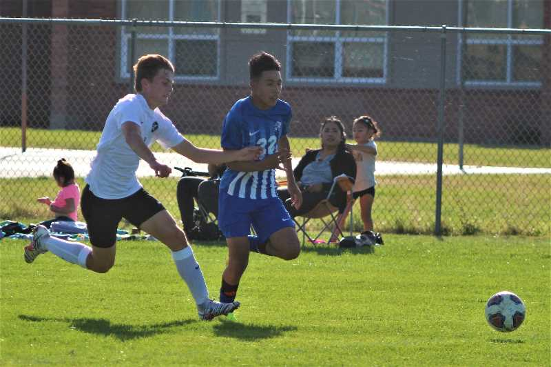 PMG PHOTO: ANDY DIECKHOFF - Madras forward Eben Tapia (22) races down the wing against an Estacada defender on Thursday evening.