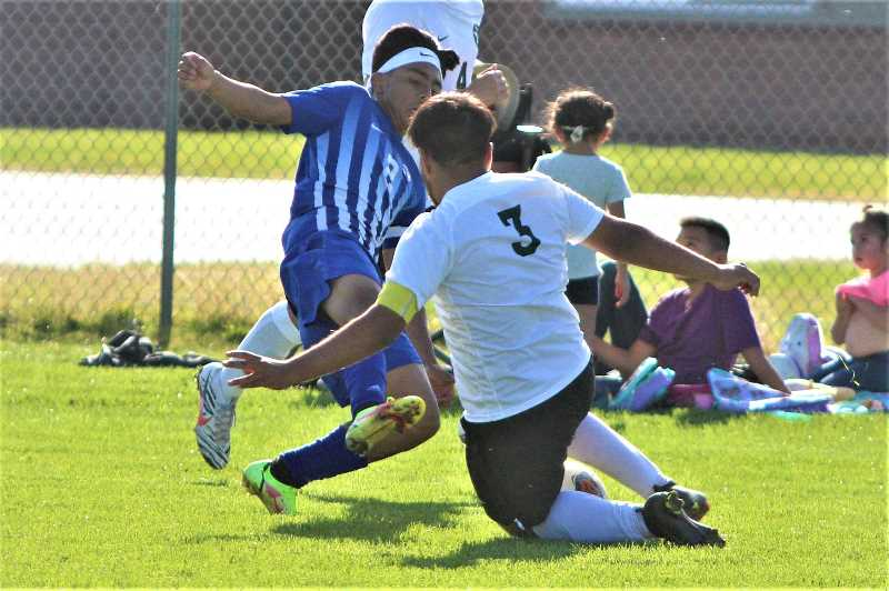PMG PHOTO: ANDY DIECKHOFF - In a collision of captains, Madras senior Luis Benitez (2) and Estacada senior Brian Reyes vie for a loose ball.