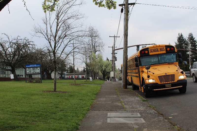PMG FILE PHOTO - A school bus waits in front of a Southeast Portland elementary school in 2021. Portland Public Schools kicked off the 2021-22 school year facing a shortage of bus drivers.