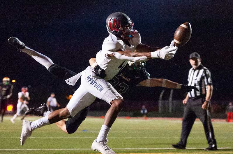 PMG PHOTO: JOHN LAVIRIERE - Westview's Darrius Clemons reaches for a pass during the Wildcats' game against Jesuit Friday night, Sept. 24, at Jesuit High School.