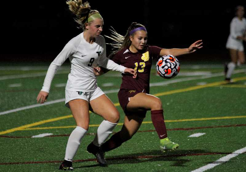PMG PHOTO: WADE EVANSON - Forest Grove senior Venezia Pazos Castaneda battles a Tigard defender for the ball during the Vikings' match versus the Tigers Wednesday, Sept. 29, at Forest Grove High School.