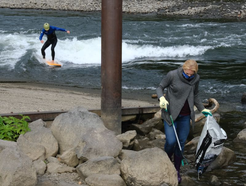 PMG PHOTO: JAELEN OGADHOH - A volunteer cleans up litter along the Clackamas River. Reducing water pollution allows residents to enjoy recreational river activities such as bodyboarding, WES officials say.