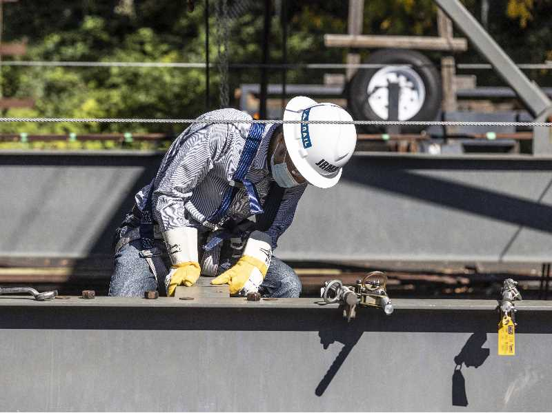 PMG PHOTO: JONATHAN HOUSE  - Nana Ochiai inspects a steel beam during SteelDay. It was organized by the American Institute of Steel Construction to give engineers and architects and others a feel for steel.