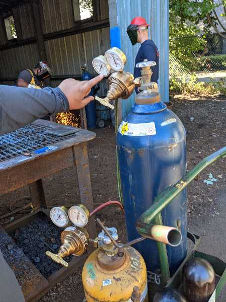 PMG PHOTO: JOSEPH GALLIVAN - At SteelDay, people got to try out mixing gas pressures in oxygen acetylene welding. Increasing the oxygen pressure (blue tank) makes the metal oxidize rapidly and fall apart in cutting.
