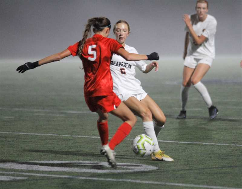 PMG PHOTO: WADE EVANSON - Beaverton senior Emily Rice and Westview sophomore Erin Kindred chase down a loose ball during the two teams' match Thursday night, Sept. 30, at Westview High School.