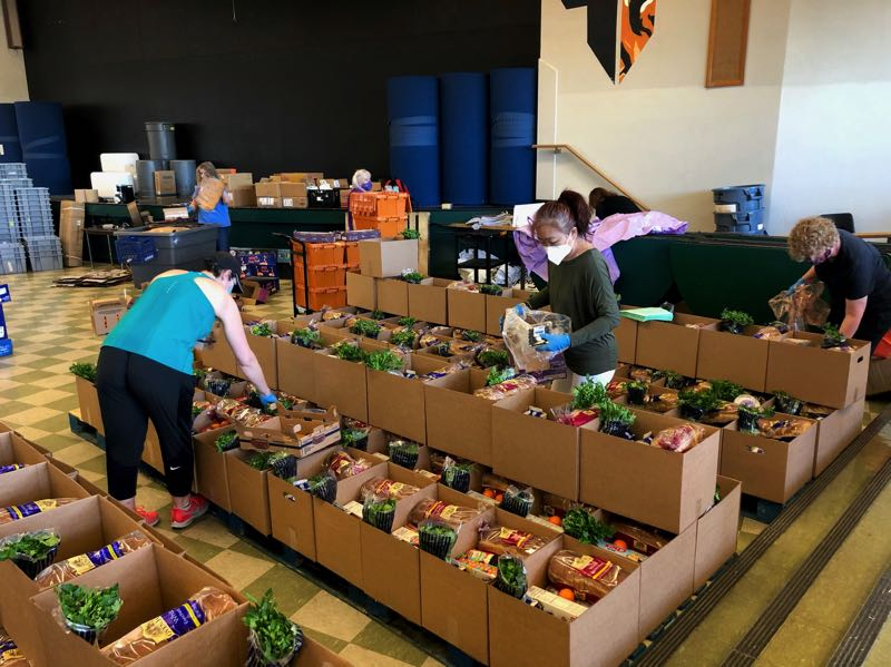 COURTESY PHOTO - Margie Yemoto-Greene helps add to a food box in the old Tigard High School cafeteria where Packed with Pride meets to put the boxes together weekly.
