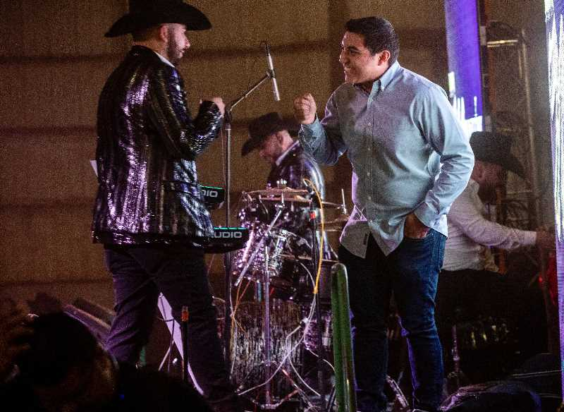 PMG PHOTO: JAIME VALDEZ - Jonathan Villagomez gives knuckles to Bobby Sigala, former keyboard player with Grupo Montez de Durango, after Villagomez played the keyboard for the first time with the band in Hillsboro this summer. Villagomez replaced him just after that weekends shows.