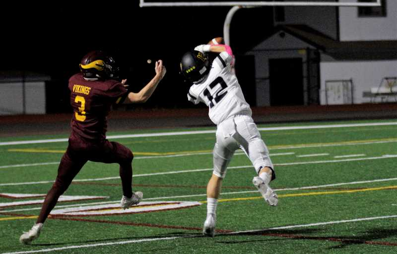 PMG PHOTO: WADE EVANSON - St. Helens receiver Dylan Shafer steals a pass away from Forest Grove defender Trevor Cannon during the two teams' game Friday night, Oct. 1, at Forest Grove High School.