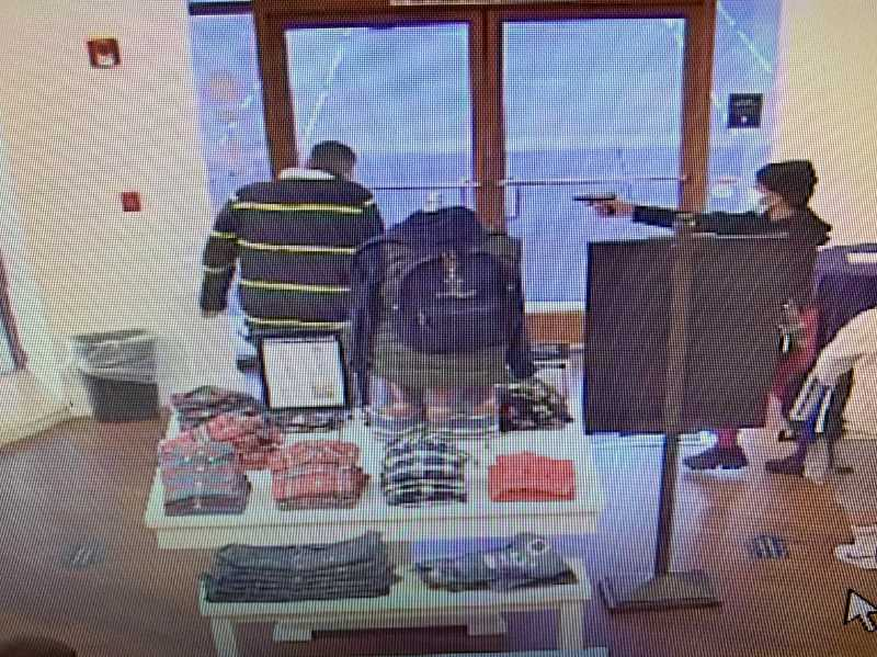 COURTESY PHOTO: WOODBURN POLICE - Armed robbery suspect points a pistol at a store employee at the Woodburn Premium Outlets.