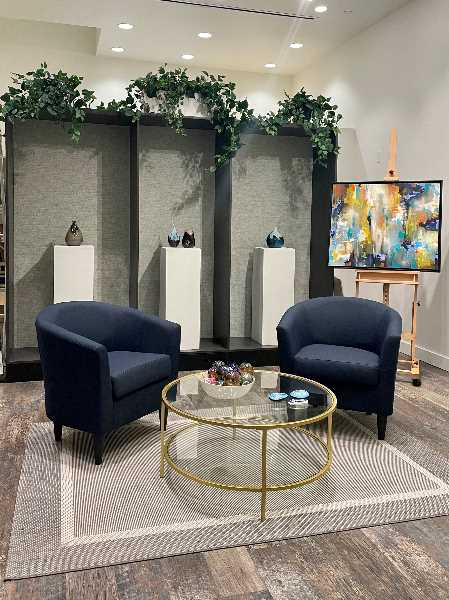 COURTESY PHOTO: JENNIFER PEPIN - The interior of J. Pepin Gallery includes a cozy living-room feel complete with a coffee table and blue chat chairs.