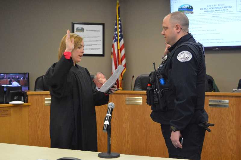 PMG PHOTO: NICOLE THILL-PACHECO - St. Helens Municipal Judge Amy Lindgren, left, swears in a new member of the police Department.