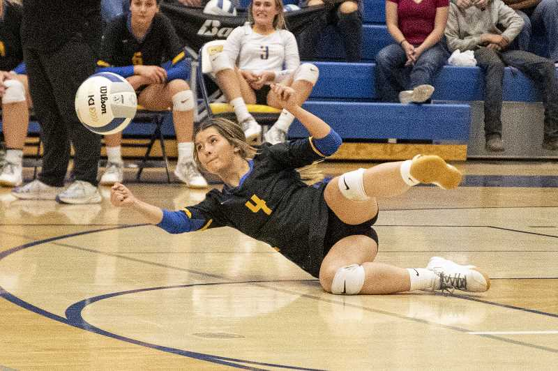 LON AUSTIN - Alexys Wells goes to the floor to keep a point alive for the Cowgirls during their five-set loss to Ridgeview in Prineville Sept. 28. Two days later, the Cowgirls were in another five-set battle, but beat Redmond.