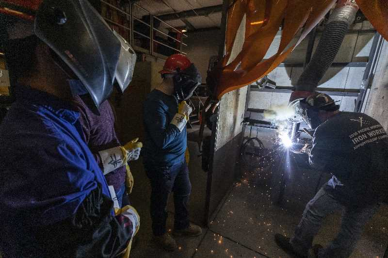 PMG PHOTO: JONATHAN HOUSE - People interested in ironworking try electric arc welding on SteelDay in welding booths at Ironworkers Local 29.