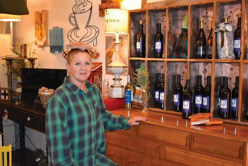 RAMONA MCCALLISTER - Connie Stewart, owner of Sage Door, stands in front of the display of Catman Cellars wine, which is displayed on one of the pieces for sale at her store. Behind Stewart are other delightful treasures for sale, many of which are provided by her consigners.