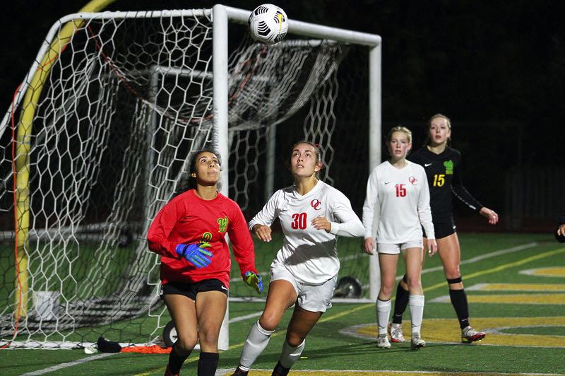 PMG PHOTO: MILES VANCE - West Linn junior goalkeeper Tori Garcia (left) and Oregon City senior Rachel Remsburg get ready to vie for control of the ball during the Lions' 2-1 win at West Linn High School on Wednesday, Oct. 6.
