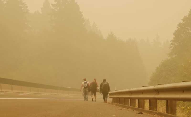 PHOTO COURTESY: OUTSIDE THE FRAME - The thumbnail for 'Riders on the Storm' features unhoused community members walking down a highway shoulder clouded in wildfire smoke after Metro employees were unable to find them temporary housing.